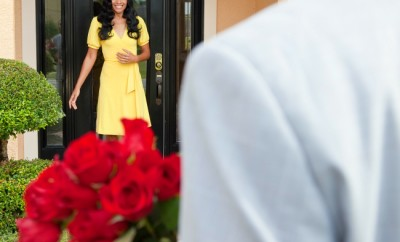 A romantic African American man bringing flowers to his happy wife or girlfriend who is standing waiting for him at the door of their home.